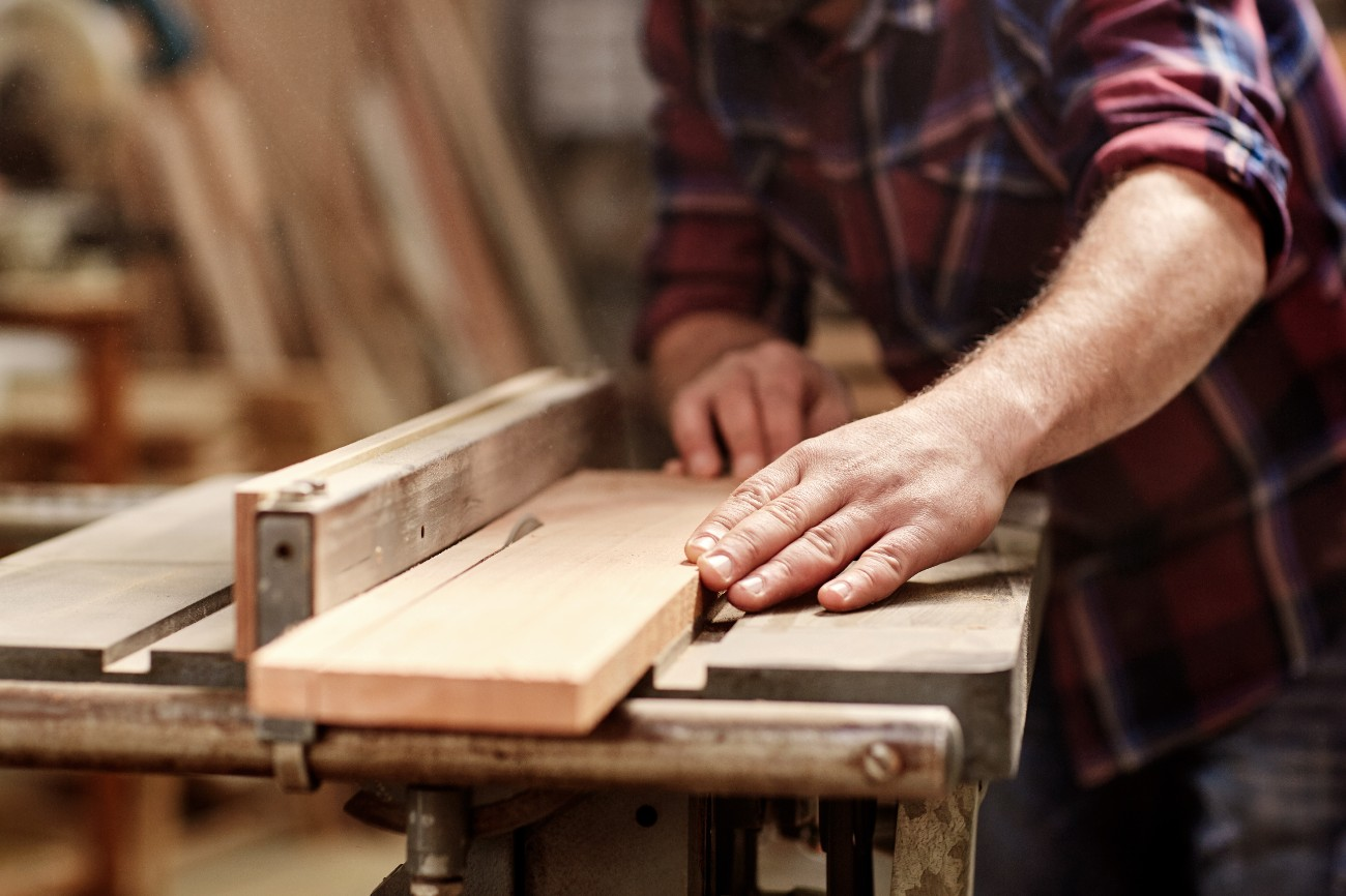 image of the hands of a skilled craftsman cutting a wooden plank