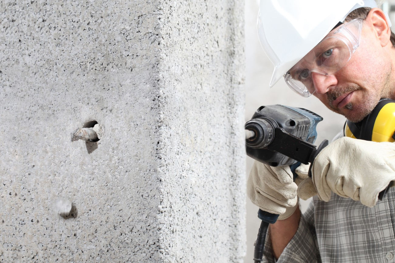 man using an electric pneumatic drill making a hole in wall, professional construction worker with safety hard hat, hearing protection headphones, gloves and protective glasses