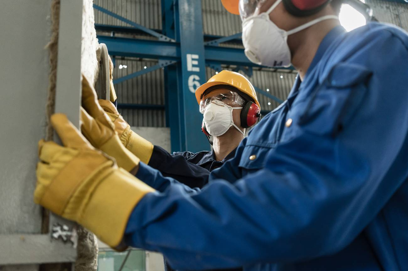 Two blue-collar workers wearing protective equipment while insulating an industrial pressure vessel